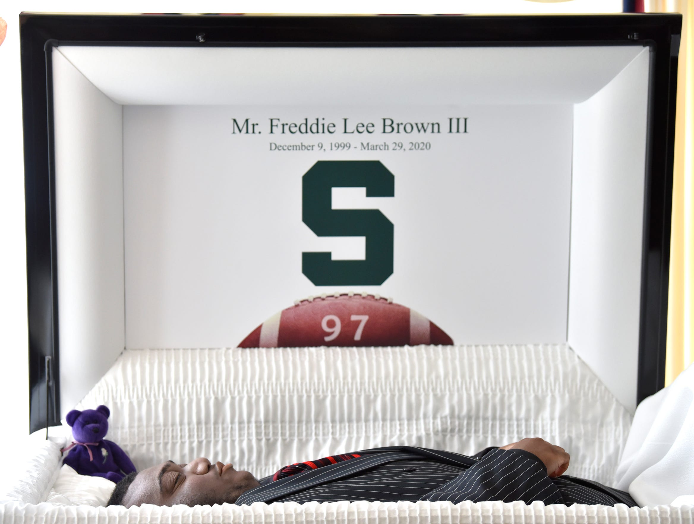"""A Michigan State University block """"S"""" and his Grand Blanc High School No.  97 is seen on the casket lid of Freddie Lee Brown III. According to family members, Brown III dreamed of playing football at MSU as a walk-on with hopes of someday playing in the NFL."""