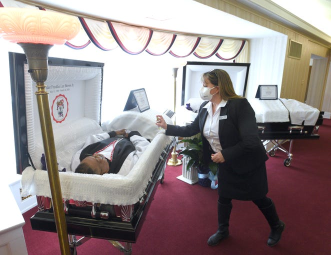 Following the wishes of wife and mother Sandy Brown (not pictured), funeral home owner Melissa Butts sprays Freddie Lee Brown Jr.'s casket with the cologne Aramis, Brown Jr.'s favorite. Butts also sprayed Freddie Lee Brown III's casket with his favorite fragrance, Guilty by Gucci. The father and son died three days apart from COVID-19 and are laid to rest together on Friday, April 10, 2020.
