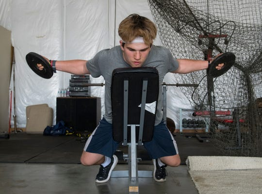 Maximus Bell does strength and conditioning exercises in his home gym on the West Side of Evansville, Ind., Monday afternoon, April 6, 2020. The Reitz High School sophomore maintains a workout schedule with a makeshift gym in his barn since there's no in-person instruction allowed with schools closed for the remainder of the academic year due to the spread of COVID-19.