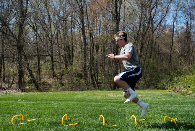 Maximus Bell runs through agility training exercises in his backyard on the West Side of Evansville, Ind., Monday afternoon, April 6, 2020. The Reitz High School sophomore maintains a workout schedule with a makeshift gym in his barn since there's no in-person instruction allowed with schools closed for the remainder of the academic year due to the spread of COVID-19.