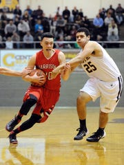 Harrison's Ernie Duncan tries to drive past Central's Dante Emerson in the second half of a game at Central High School in Evansville on Wednesday, December 11, 2013.