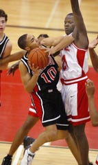 Harrison's Melvin Hall tries to drive to the basket as Pike's Robert Vaden looks for a block during first half action at Southport High School on Saturday, March 22, 2003. Evansville Harrison took on No.1-ranked Indianapolis Pike during the Class 4A Semistate in Indianapolis.