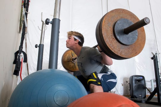 Maximus Bell squats 335 lbs. in his home gym on the West Side of Evansville, Ind., Monday afternoon, April 6, 2020. The Reitz High School sophomore maintains a workout schedule with a makeshift gym in his barn since there's no in-person instruction allowed with schools closed for the remainder of the academic year due to the spread of COVID-19.