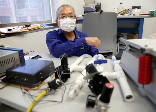 Samsun Lampotang, professor of anesthesiology at the University of Florida College of Medicine, kneels beside two ventilators he and his team have developed from readily available retail parts. He hopes hospitals overwhelmed by coronavirus patients may soon be able to build their own.