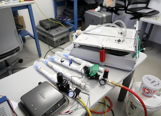 Two of UF's do-it-yourself ventilators sit between an Arduino controller, housed under a baking pan. at the lower left, and machine, at upper right, that simulates the lungs of two patients. The H-shaped ventilators are built from parts available at home improvement stores: PVC pipe, lawn-sprinkler valves and a regulator for an air compressor.