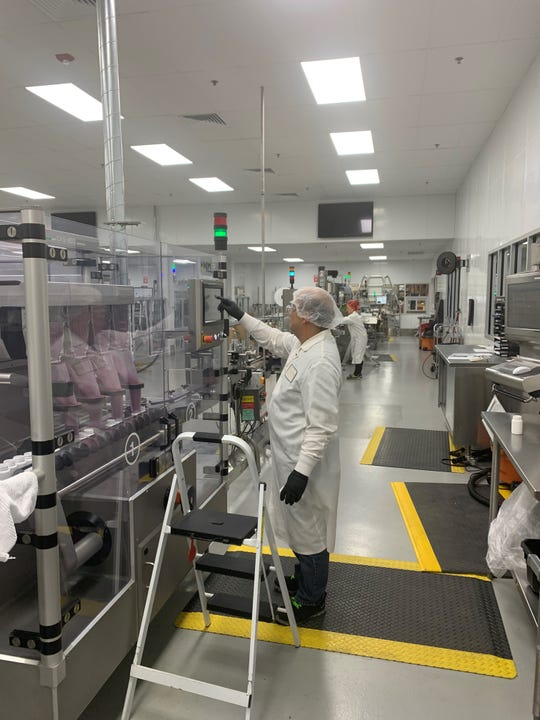 Chong Yang, foreground, and Ger Vang, background, wear gloves, hairnets and other personal protective equipment while working at Nature's Way's Green Bay manufacturing plant. The company produces dietary supplements, vitamins and other health supplements. It has ramped up production to match increased demand for immune system supplements during the coronavirus pandemic.