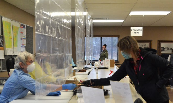 A voter wearing a mask and gloves takes her ballot slip from poll worker Connie Yost at the Little Suamico Town Hall on Tuesday.