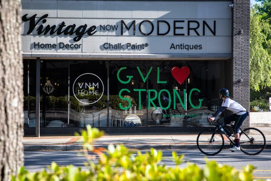 A cyclist looks at a message written on a storefront window on South Main Street in Greenville, Friday, April 10, 2020.