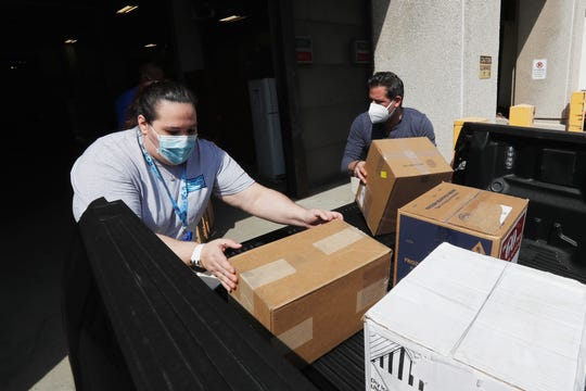 Christina Caldwell, left, of Henry Ford Population Health helps unload supplies with Matt Thatcher, who donated them from the Detroit Golf Club, Wednesday, April 8, 2020, in Detroit. The hospital is also in need of gowns and other PPE items and hopes more donations will be coming in from others to help during the coronavirus pandemic. (AP Photo/Carlos Osorio)