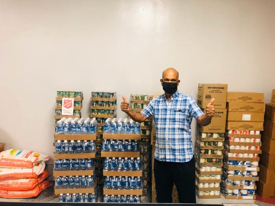 """Thiruchelvam """"Thiro"""" Vadivel from Nayon Express and the UOG cafeteria stands by boxes of donated food items. He has been preparing around 200 meals per day for health care workers."""