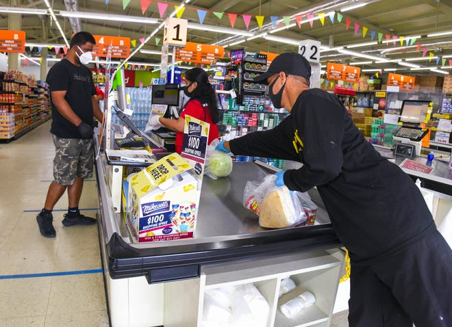 Piti Mayor's Office employee, Mark Reyes, right, collects bagged goods as fellow worker, Chris Ofalla, pays for the items at the Day Buy Day supermarket in Piti after shopping for a village manåmko', or senior citizen, at the store on Friday, April 10, 2020.
