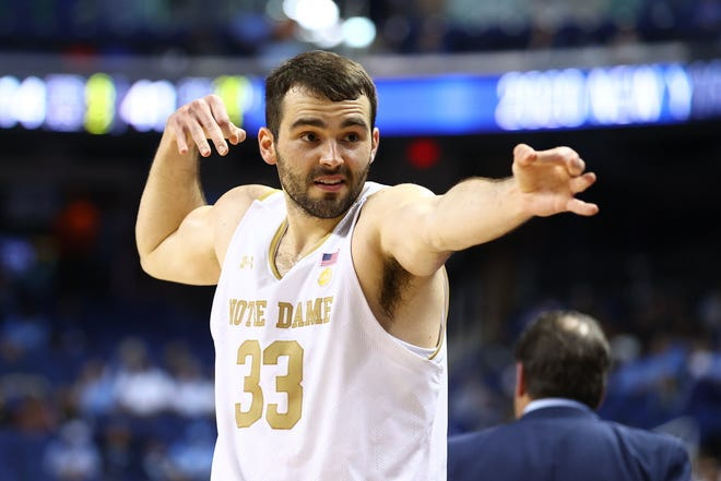 Notre Dame Fighting Irish forward John Mooney (33) celebrates on the bench after a Fighting Irish basket against the Boston College Eagles during the second half at Greensboro Coliseum.