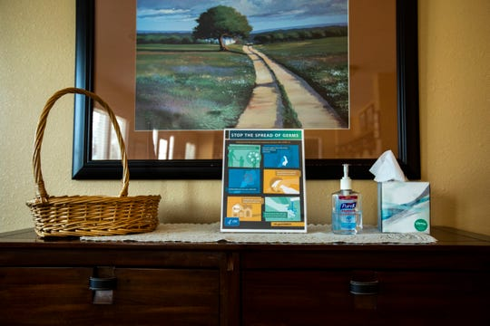 """A Centers for Disease Control and Prevention (CDC) informational graphic, """"Stop the spread of germs,"""" is seen alongside a bottle of Purell hand sanitizer, Friday, April 10, 2020, at Gay & Ciha Funeral Home in Iowa City, Iowa."""