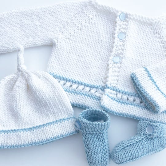 A white sweater and hat, trimmed in blue, and coordinating blue booties, all knitted by Becky Mercier, make a perfect gift for a baby shower.