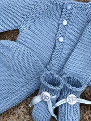 Monogramed buttons add flair to a pair of booties Becky Mercier of Madison knitted for a baby boy to wear with a matching sweater and hat.
