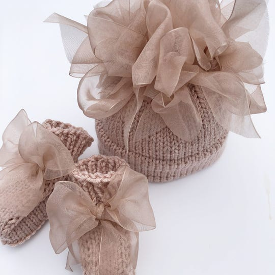 Large bows finish off a pair of booties Becky Mercier of Madison knitted for a babygirl to wear with a matching sweater and hat.