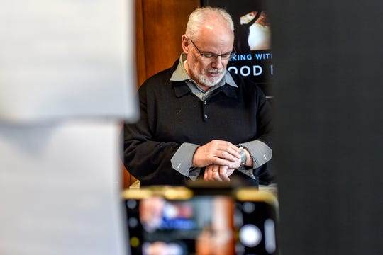 The Rev. Rick Blunt checks the camera from his watch as he prepares to record his daily devotional for the online congregation at the Okemos Community Church on Friday, April 10, 2020, in Okemos. The church is using technology to provide church services to people during the coronavirus.