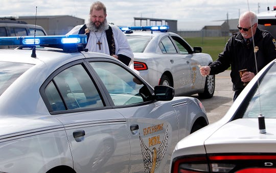 Pastor Rich Rader from Mayflower Congregational Church and Rev. Daniel Vickey, Ohio State Highway Patrol Regional Chaplain from the Bucyrus District, bless vehicles with holy water at the  Blessing of the Badges at Richland Aviation at Mansfield Lahm Airport Friday