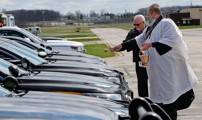 Rev. Daniel Vickey, Ohio State Highway Patrol Regional Chaplain from the Bucyrus District, and Pastor Rich Rader from Mayflower Congregational Church bless the vehicles with Holy Water at the  Blessing of the Badges at Richland Aviation at Mansfield Lahm Airport Friday.