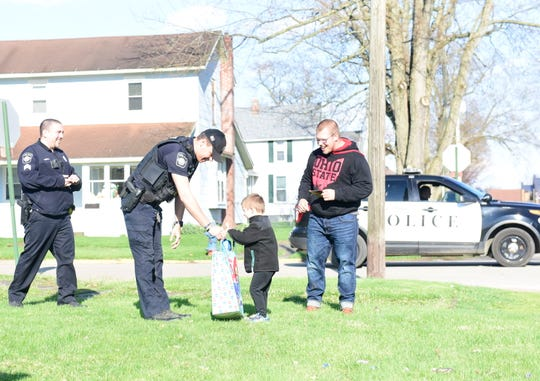 Camden Duncan gets a bag of gifts Thursday for his 5th birthday from Patrolman Chase Cooke of the Crestline Police Department.