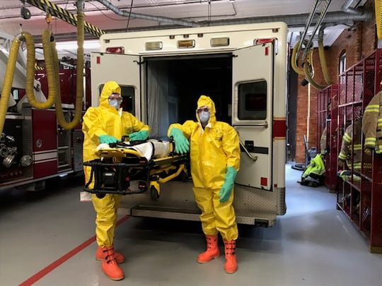 Members of the Marion Fire Department COVID-19 response team are shown in full gear. The team will respond to emergency calls involving potential coronavirus patients. Nine firefighters volunteered to be part of the detail.