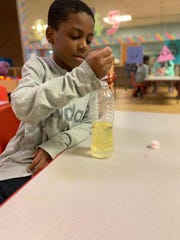Children in the YMCA of Metropolitan Milwaukee's emergency child care program spend some of their time doing science experiments at socially distant tables.