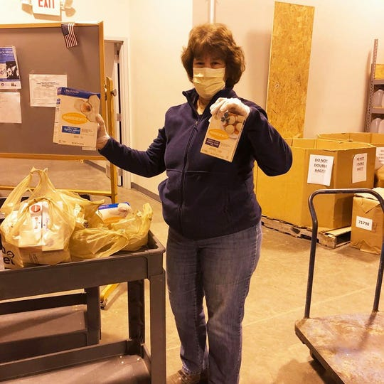 A food drive volunteer holds up items found in a Passover Seder. The Jewish Community Pantry served as the site to pack 400 meal kits that would be delivered to Milwaukee-area families.