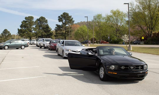 Cars line up in the Nelson-Wilks-Herron Elementary before proceeding to Charlie and Dorothy Rhea's house on April 8.