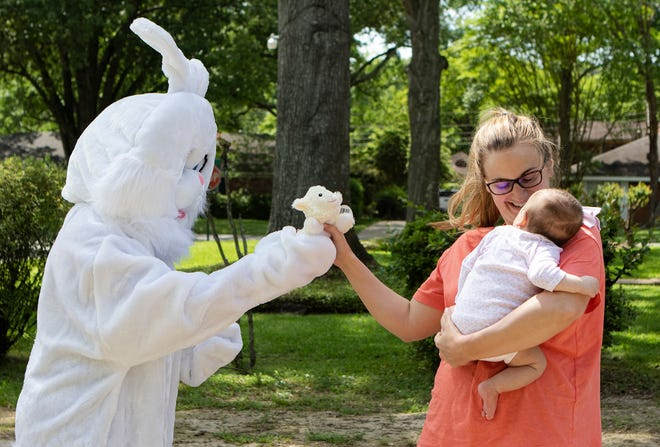 Victoria Christy, dressed as the Easter Bunny gives Kelsi Dickerson a stuffed animal for her 2 month-old daughter Haley in Monroe, La. on Good Friday, April 10. Christy was supposed to have an Easter party, but it had to be cancelled due to social distancing and the coronavirus.