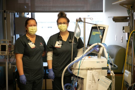Respiratory therapists Sabrina Bowman, left, and Shelby Wynk, stand next to a ventilator ready for an incoming patient in the intensive care unit on Wednesday April 8, 2020.