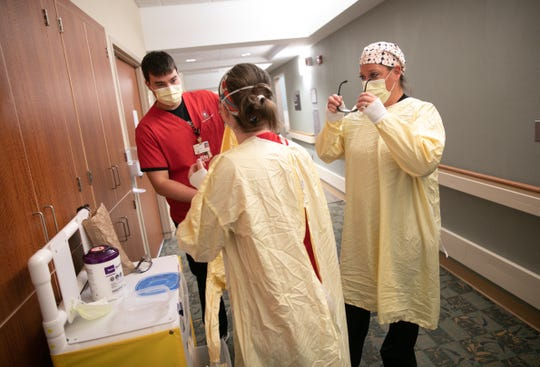 Parker May, RN, intensive care unit, dons personal protective equipment before entering a COVID-19 patient's room on Wednesday April 8, 2020.