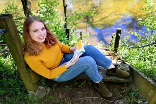 Sally Smith sits in one of her favorite places to read near the Stones River at her home on Friday, April 10, 2020, in Murfreesboro, Tenn.  Smith had to come back home from Kenyon College in Ohio her freshman year to finish up at home online this semester due to the coronavirus.