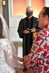 Minister Jerry Hendrixson wheres a mask as he performs the ceremony for Heather Helton and Lewis Burwell who had to cut their big wedding down to a small one because of the covid-19 restrictions in Donelson, Tenn. Friday, April 10, 2020.