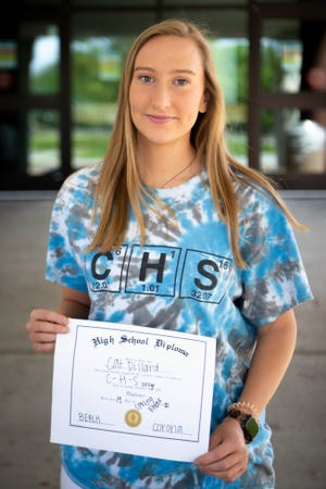 """Centennial High School senior Cat Dillard, 18, poses for a portrait with her homemade """"diploma"""" at Centennial High School Thursday, April 9, 2020, in Nashville, Tenn."""