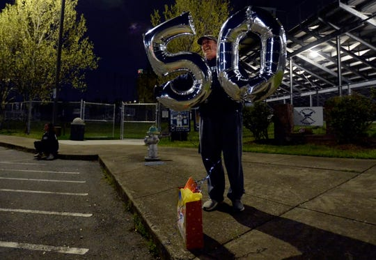 Centennial High School baseball coach Rob Baughman celebrates his 50th birthday with students at a surprise drive by on Thursday, April 9, 2020, in Franklin, Tenn. Baughman was at the school to turn the field lights on in support of student athletes to show that coaches are thinking of them during the COVID-19 pandemic. The baseball season was cut short when school and athletic activities were canceled.