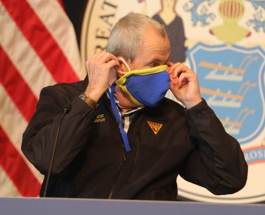 New Jersey Governor Phil Murphy removes his mask before beginning his daily press briefing at the the War Memorial in Trenton, NJ on April 10, 2020, regarding updates on the corona virus.
