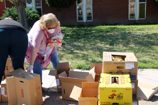 Alamogordo Mayor Pro Tem Nadia Sikes collects items to put in food boxes at the Our Savior Lutheran Roadrunner Mobile Food Bank dat Friday, April 10.  Our Savior Lutheran Church is continuing its Roadrunner Mobile Food Bank program in the age of COVID-19.