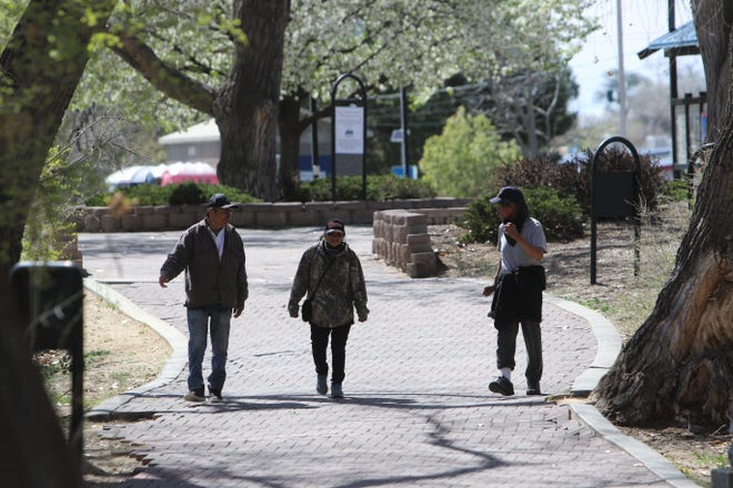 Residents walk down the trail at Berg Park on Friday, April 10, 2020, in Farmington.