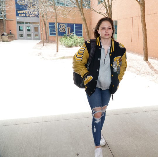 South Lyon High senior Kelsie O'Connor walks from the north end of the school on April 10, 2020. The student, like many others in her grade, are not sure if there will be a formal end to the last year of high school including prom, graduation and other notable event.s