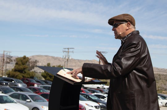 Joshua Springs Calvary Chapel senior pastor Jerel Hagerman delivers a sermon for a drive-in church service in the church's parking lot in Yucca Valley, Calif.