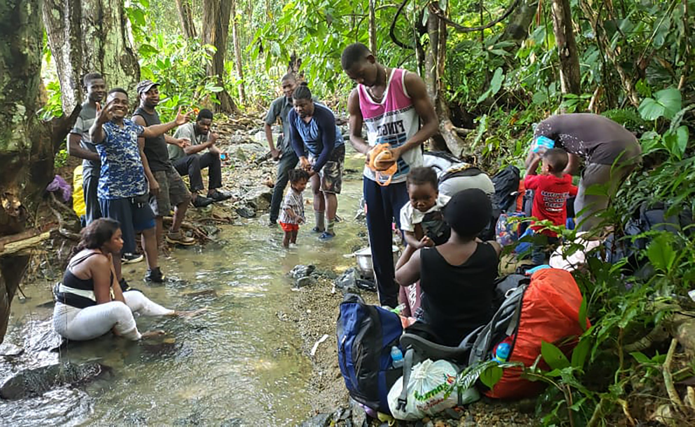 Williamson Simon, at center, holds his son as he travels north through the Darien Gap at the border between Panama and Colombia, in December 2019.