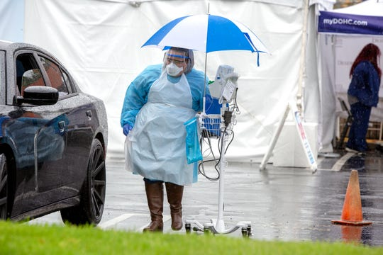 Desert Oasis Healthcare nurse Jessy Rodriguez prepares to screen people for COVID-19 at the drive up site in Palm Springs, Calif., on April 10, 2020. Rains continued throughout the day.