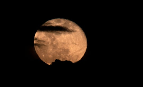 Clouds partially obscure the super moon, one day after full, in Palm Springs, Calif., on April 8, 2020.