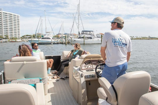 At right, Joseph Weaver, owner of Wave Cutter Charters, steers a cruise around Little Sabine Bay in Pensacola Beach on Friday. Weaver is offering 30-minute dinner cruises around the bay as people eat their take-out meals during the coronavirus pandemic.