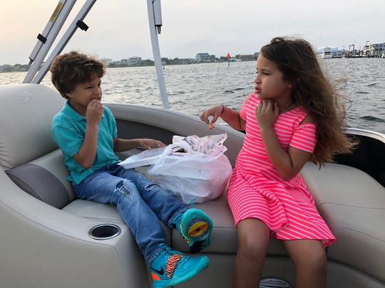 Jesiah and Eliana Demming of Pensacola Beach share a meal from Shaggy's and enjoy a dinner cruise Wednesday, courtesy of Wave Cutter Charters.