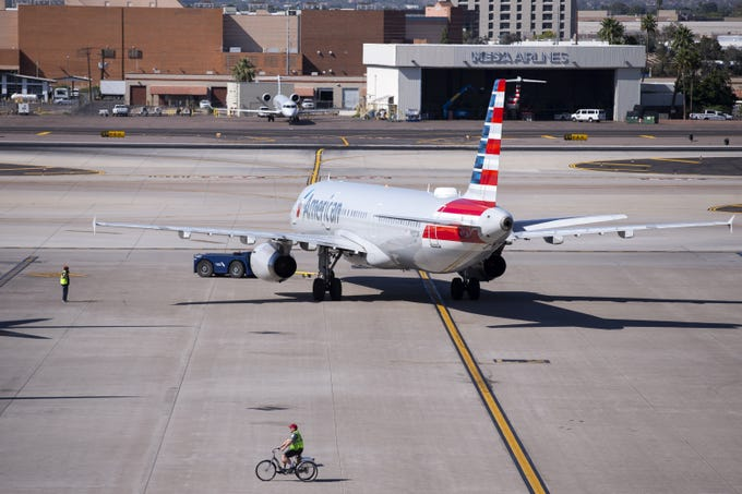An airport employee rides a bicycle on the tarmac as an American Airlines flight prepares for departure on April 9, 2020, at Sky Harbor International Airport in Phoenix.