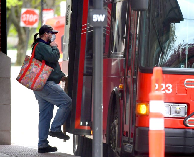 A person wearing a mask boards a bus at the Rabbit Transit bus depot Friday, April 10, 2020. All Rabbit Transit bus riders will be required to wear protective masks starting Monday, April 13. Bill Kalina photo