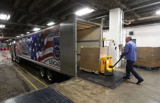 Trucks are loaded at the Riverside Convention Center as it is being cleared of products used by Foodlink as a packing site to assist community members with food distribution.