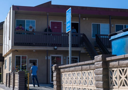 A few H2A workers hanging out n the second floor of the Budget Inn Motel in Salinas talk to a person standing just right outside their room on April 2, 2020.