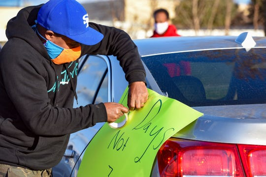 Abel Argo tapes a sign to his car before participating in a protest in solidarity with Smithfield Food, Inc. employees after many workers complained of unsafe working conditions due to the COVID-19 outbreak on Thursday, April 9, in Sioux Falls. This week, over 80 Smithfield employees tested positive for the virus, and the plant is closing for just three days before expecting workers back.